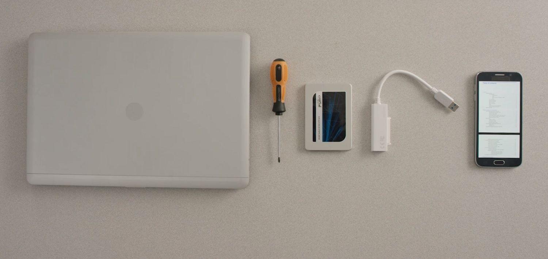 一台筆記型電腦、Crucial SSD、螺絲起子及手機上的電腦使用者手冊,一併陳列在桌面上
