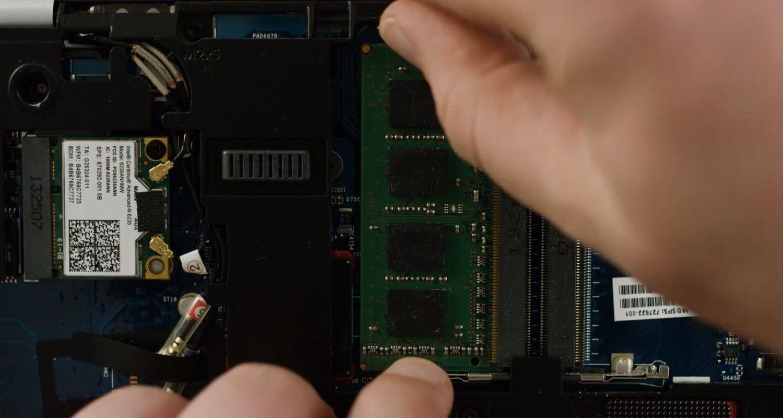 一位人士從筆記型電腦內部解開 RAM 記憶體模組扣件